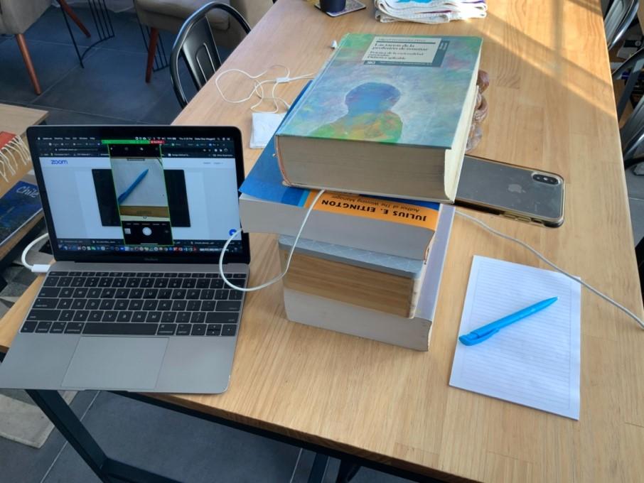 Imagen de un celular, sobre una pila de libros para que quede sostenido, y conectado a la computadora