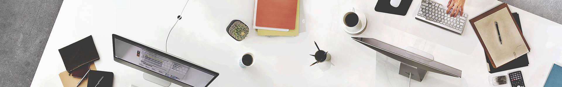 Escritorio con computadoras, libros, cuadernos, manos, vistas desde arriba
