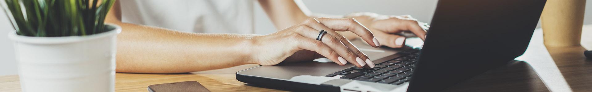 Manos de una mujer tipeando en una computadora